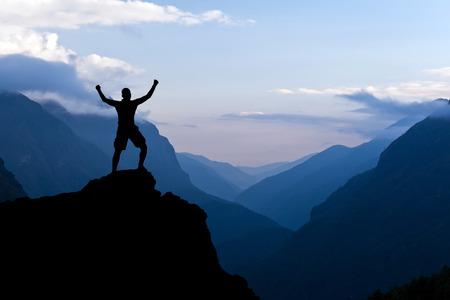 Man wandelen succes silhouet in de bergen. Mannelijke wandelaar met uitgestrekte armen op de top van de berg te kijken naar prachtige Himalaya-landschap.