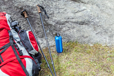 metal pole: Hiking equipment in mountains, sticks, water bottle and backpack on a rock Stock Photo