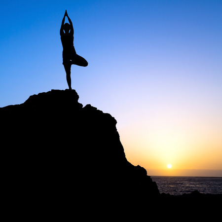 Young woman doing beautiful yoga pose tree, sunset silhouette in mountains over blue sky and clouds with sun sunlight background. Healthy lifestyle successful fitness exercise concept. photo