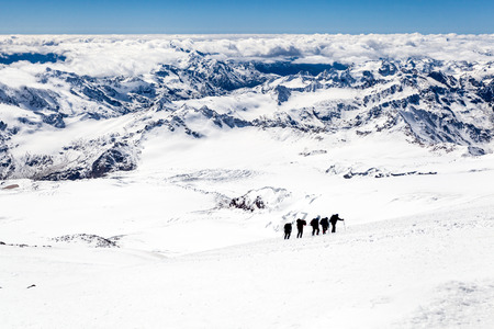 People hiking silhouette and climbing on snow in high mountain of Elbrus photo