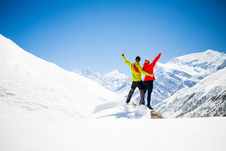 Couple hikers man and woman success in winter mountains. Inspiration and motivation in beautiful landscape. Fitness healthy lifestyle outdoors on snow in Himalayas, Nepal. Annapurna range trekking.