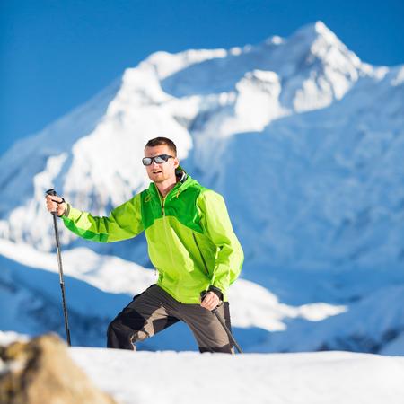 El hombre excursionista escalada explorar en altas montañas del Himalaya en Nepal. Senderismo senderismo feliz en invierno blanco o naturaleza hermosa del otoño. Annapurna pico en el fondo.