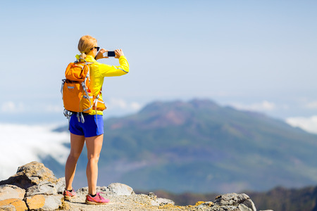 lifestyle outdoors: Hiking woman taking pictures in mountains with smart phone. Fitness and healthy lifestyle outdoors in summer nature on La Palma, Canary Islands. Using smartphone outdoor.