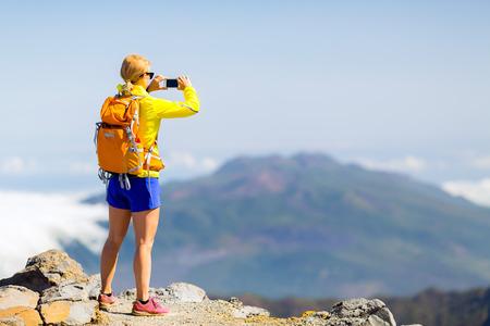 Wandern Frau, die Bilder in den Bergen mit Smartphone. Fitness und gesunde Lebensweise im Freien im Sommer Natur auf La Palma, Kanarische Inseln. Mit Smartphone im Freien.