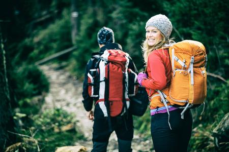 Hombre y mujer los excursionistas de trekking en las montañas. Pareja joven caminando con mochilas en el bosque, Tatras en Polonia. Estilo de foto de época antigua. Foto de archivo