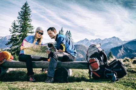 Man en vrouw wandelaars wandelen in de bergen. Jong stel kamperen, kijken naar de kaart en planning reis of verdwalen. Het krijgen van rust en het drinken van koffie of thee