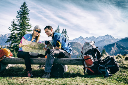 Mann und Frau Wanderer Wandern in den Bergen. Junges Paar camping, Blick auf Karte und Planungsreise oder verloren gehen. Anreise Ruhe und trinken Kaffee oder Tee