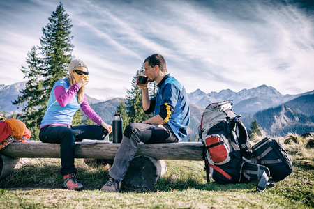Man and woman hikers hiking and drinking in mountains. Young couple looking at map and planning trip or get lost. Vintage style trekking and recreation concept Banco de Imagens