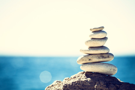 zen: Stones balance, vintage retro instagram like hierarchy stack over blue sea background. Spa or well-being, freedom and stability concept on rocks.