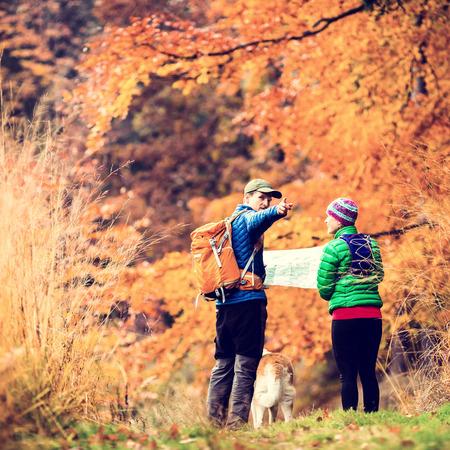 planificación familiar: Hombre y mujer los excursionistas de senderismo en el bosque de otoño colorido con el perro akita. Pareja joven busca en el mapa y la planificación del viaje o se pierde, la foto de estilo retro vendimia Instagram