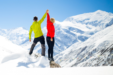 group goals: Couple hikers man and woman success in winter mountains, sport climbing. Inspiration and motivation in beautiful landscape. Fitness healthy lifestyle outdoors on snow in Himalayas, Nepal. Annapurna range trekking.