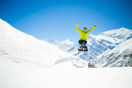 Happy young male hiker jumping in white snowy winter mountains Himalayas.  Success climbing on snow, beautiful landscape with Annapurna peak in backgound photo