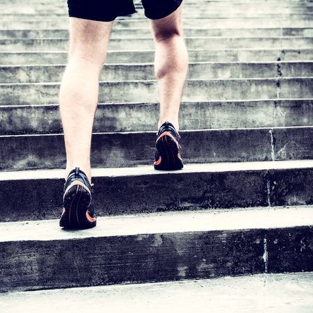 concrete stairs: Man runner running on stairs in city, sport training. Young male jogger athlete training and doing workout outdoors in city. Fitness and exercising outdoors urban environment.