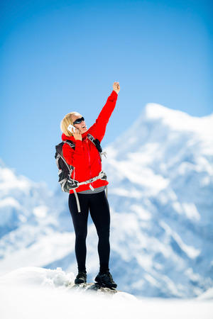 Young happy woman hiker talk on the phone on mountain peak summit in winter mountains. Climbing inspiration and motivation, beautiful landscape. Fitness healthy outdoors activity in Himalayas, Nepal photo