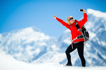 Young happy woman hiker doing selfie self-portrait on mountain peak summit in winter mountains. Climbing inspiration and motivation, beautiful landscape. Fitness healthy lifestyle outdoors on snow in Himalayas, Nepal. Annapurna range trekking. photo
