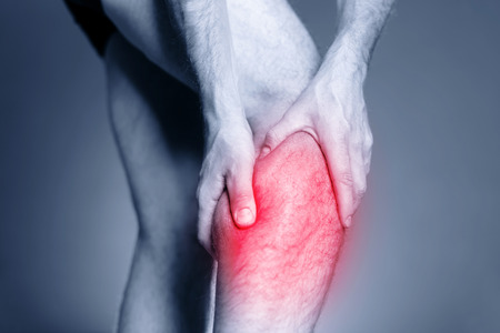 Calf leg pain, man holding sore and painful muscle, sprain or cramp ache filled with red pink bright place. Person injured when exercising or running
