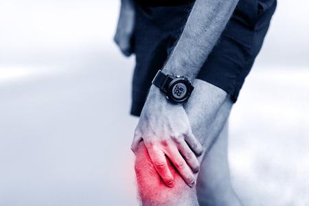 de rodillas: El dolor de rodilla, pierna corredor y dolor muscular en ejecución y capacitación al aire libre, deporte y recreo lesiones físicas cuando se trabaja fuera. Atleta masculino que sostiene la pierna dolorosa. Foto de archivo
