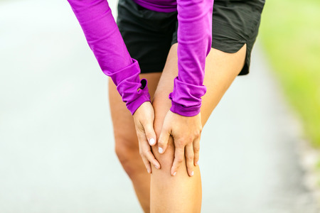 Female runner leg and muscle pain during running outdoors in summer nature, sport jogging physical injury, working out outside holding sore knee joint. Health and fitness concept, accident when training Reklamní fotografie - 34028120