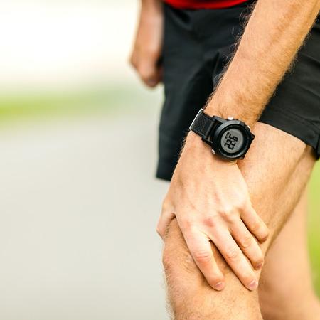 artrosis: El dolor de rodilla, pierna corredor y dolor muscular en ejecución y capacitación al aire libre, deporte y recreo lesiones físicas cuando se trabaja fuera. Atleta masculino que sostiene la pierna dolorosa. Foto de archivo