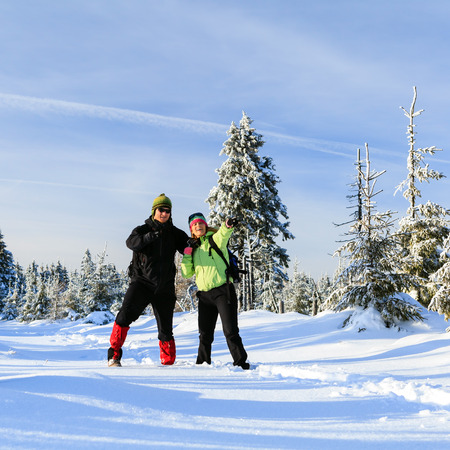 winter couple: Happy man and woman hikers trekking on snow trail in winter mountains. Young couple on white and cold vacations in winter forest, beautiful natural landscape.