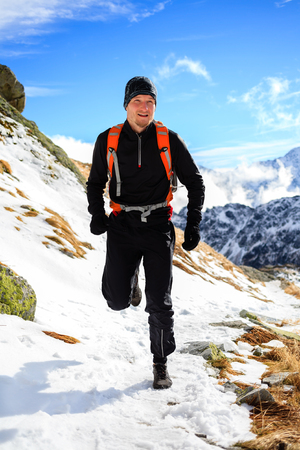 ultra: Young man trail running in mountains on winter or fall sunny day. Male athlete cross country runner training for ultra distance outdoors in cold snow nature.