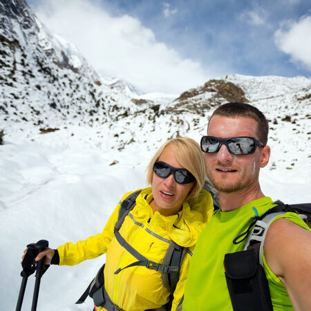himalayas: Couple hikers man and woman doing selfie portrait on expedition in winter mountains. Inspiration and motivation. beautiful nature landscape. Fitness healthy lifestyle outdoors on snow in Himalayas, Nepal, Annapurna range trekking.