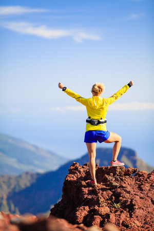 Climbing hiking or trail cross country running woman and success in mountains. Fitness and healthy lifestyle outdoors in summer nature. Achievement and motivation, reaching goals outside with arms outstretched.