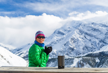 thermos: Young woman hiker drink coffee or tea in beautiful Himalaya mountains on hiking trip, Nepal. Active person resting outdoors in winter white nature using cup and thermos on wooden table in base camp.