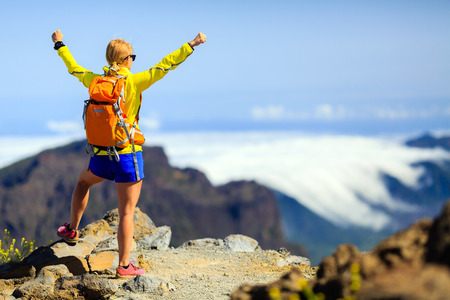 winning woman: Hiking woman and success in mountains. Young female backpacker celebrating on mountain top. Fitness and healthy lifestyle outdoors in summer nature on La Palma, Canary Islands Stock Photo