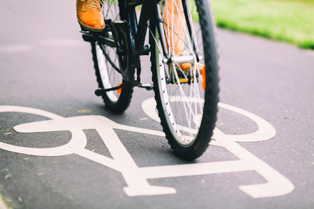 都市環境で自転車に通勤シティ自転車サイクリング道路、通り、点灯のカラフルなヴィンテージのアスファルト深川側男サインオン