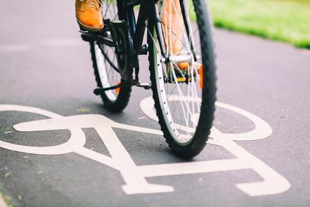 City-Bike Zeichen auf Asphalt Radweg Mann Radfahren auf Straße, bunte Vintage Licht auf der Straße, Pendeln, um mit dem Fahrrad in städtischen Umfeld zu arbeiten