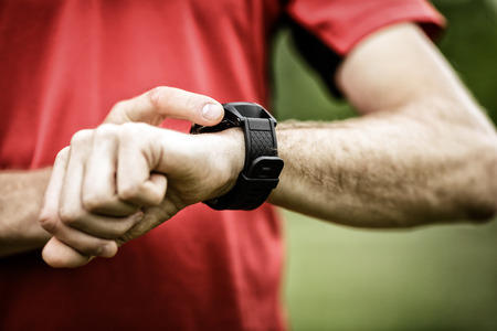 Runner na górskim szlaku, patrząc na zegarek SmartWatch lub sport, sprawdzanie położenia mapy nawigacji GPS lub tętna ślad impulsu, przy użyciu sprzętu monitora pracy serca. Sport i fitness na zewnątrz w przyrodzie.