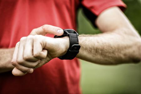 cuore: Runner sul sentiero di montagna guardando smartwatch o vigilanza di sport, il controllo gps navigazione mappa la posizione o la frequenza cardiaca Elettrocardiogramma, utilizzando attrezzature monitor cardiaco. Sport e fitness all'aperto in natura.