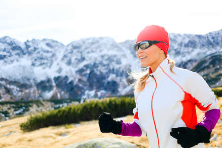 ultra: Young woman running in mountains on winter or fall sunny day. Happy beautiful female runner exercising outdoors in nature, using black sunglasses for sunset. Healthy lifestyle outside adventure and achievement.