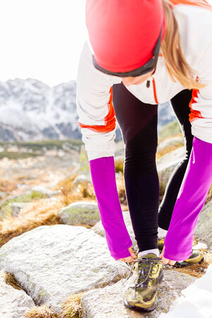 Young woman running in mountains on winter fall sunny day. Female runner tying sports shoe. Motivation and inspiration concept fitness exercising outdoors adventure.