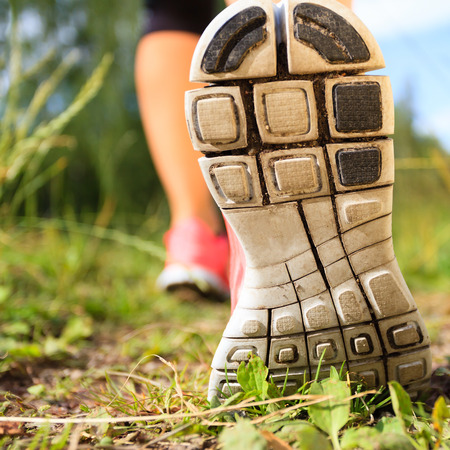 the sole of the shoe: Walking or running exercise shoes close-up, legs on green grass footpath in forest, achievement fitness adventure and exercising in spring or summer nature Stock Photo