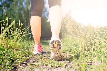 persona cammina: Camminare o correre esercizio, gambe sull'erba verde sentiero nella foresta, la realizzazione avventura fitness e l'esercizio in primavera o in estate la natura