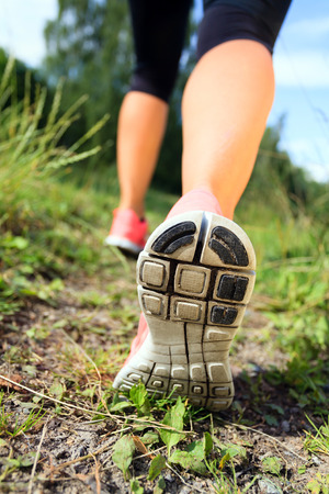 trail: Walking or running exercise, legs on footpath green grass in forest, achievement fitness adventure and exercising in spring or summer nature Stock Photo