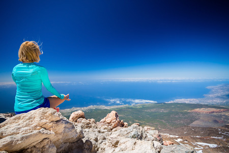 mountains and sky: Young woman doing yoga meditation outside natural beautiful inspirational environment, fitness and exercising motivation and inspiration in sunny mountains over blue sky and ocean sea. Stock Photo
