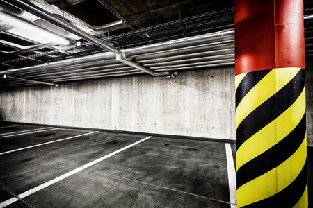 parking lot interior: Parking garage underground interior background or texture. Concrete grunge wall and column with warning sign, industrial retro vintage interior. Stock Photo