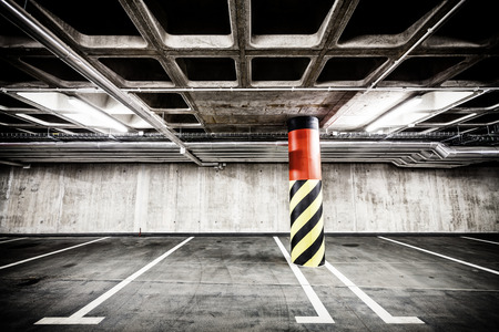parking garage: Parking garage underground interior background or texture. Concrete grunge wall and column with warning sign, industrial retro vintage interior. Stock Photo