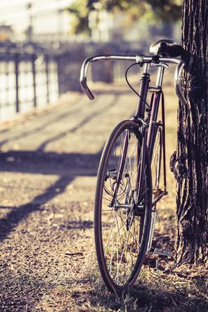 Fixed gear fiets. Weg fiets op straat in de stad. Groen park en bomen fiets buiten stedelijke scène onder een boom kopie ruimte en ondiepe scherptediepte Vintage oude retro fiets fietsen ecologie of woon-werkverkeer in de stad stedelijke omgeving