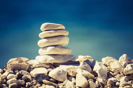 Balance und Spa-Konzept Zenlike Inspiration und Wohlbefinden ruhige Komposition. Wellness Harmonie weißen Stein Kieselsteinen Stapel über blauen Meer