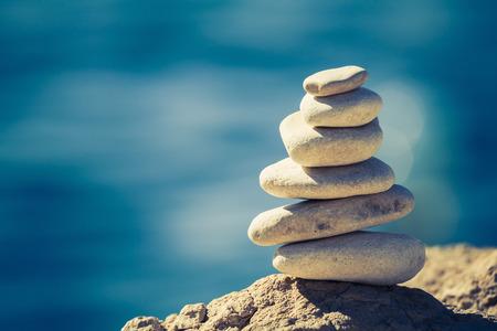 concepto equilibrio: Equilibrio y bienestar concepto de spa de inspiraci�n retro zenlike y bienestar composici�n tranquilo. Primer plano de la pila de guijarros blancos sobre el mar azul