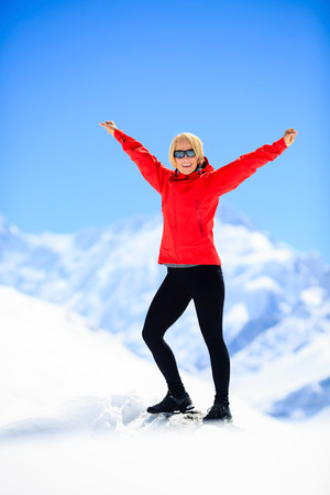 Young happy woman hiker portrait on mountain peak summit in winter mountains. Climbing inspiration and motivation beautiful landscape. Fitness healthy lifestyle outdoors on snow in Himalayas Nepal. Trekking the Annapurna range. photo