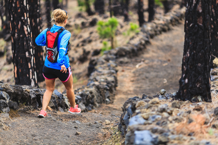 ultra: Young woman running in mountain forest on sunny summer day. Female runner exercising outdoors in beautiful nature run or hike concept.