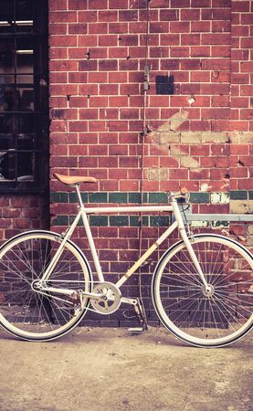 City bicycle fixed gear and red brick wall vintage bike. Retro stylish cycling in town old retro fix cycle cycling or commuting in city urban transportation concept ecological environment photo