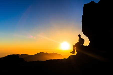 motivation: Man hiking in mountains silhouette sunset and ocean views. Male hiker with backpack on top of a mountain looking at beautiful night landscape view and blue sky freedom concept Stock Photo