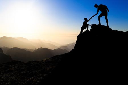 登る: 信頼をハイキング チームワーク カップルを助ける山日没のシルエットの相互支援。お互いに助け合って、登山の上に美しい日没の風景を信頼登山男性と女性ハイカーのチーム。