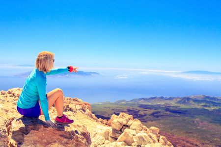 woman mountain: Young woman looking at natural beautiful inspirational landscape with islands and ocean hiking trekking and recreation motivation and inspiration in sunny mountains over blue sky and ocean sea Canary Islands.